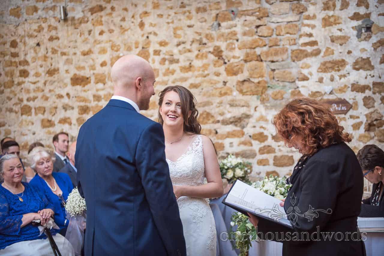 Exchange of wedding rings photograph at Tithe Barn wedding ceremony on Symondsbury estate