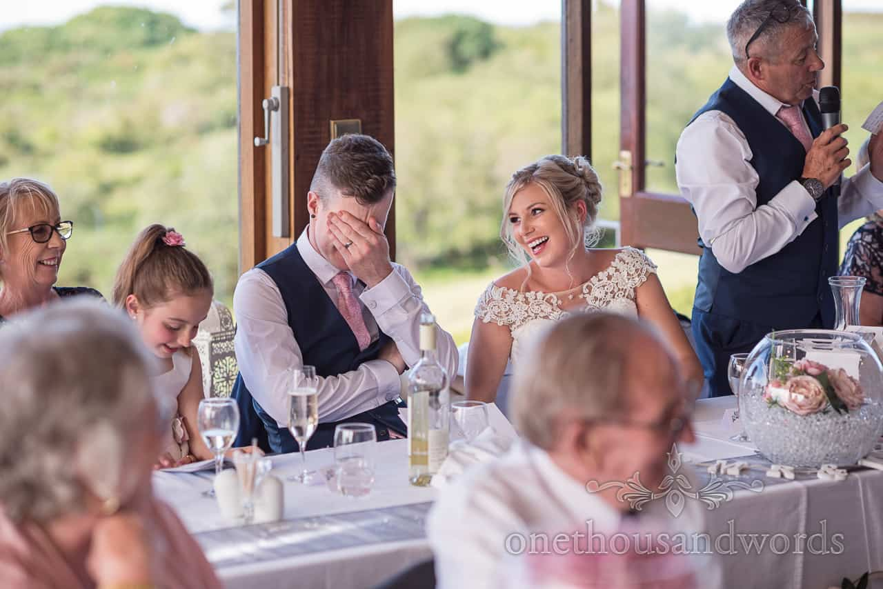 Shamed groom holds his head in his hands at top table during wedding speeches by the father of the bride as bride laughs at him