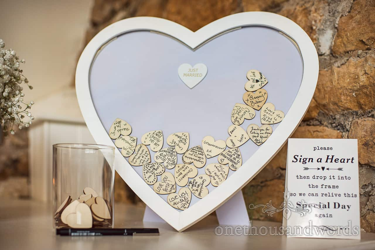 Detail wedding photograph of signed wooden love hearts in love heart frame as wedding guest book idea.