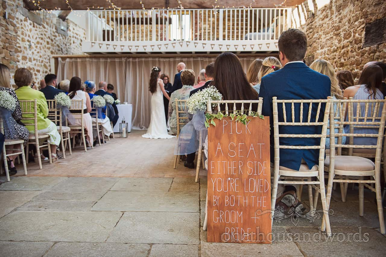 Pick a seat either side you're loved by both the groom and bride wooden sign at Tithe Barn Dorset wedding ceremony photograph