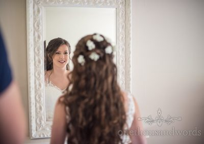 Smiling bride checks herself in ornate white framed mirror during wedding morning preparations