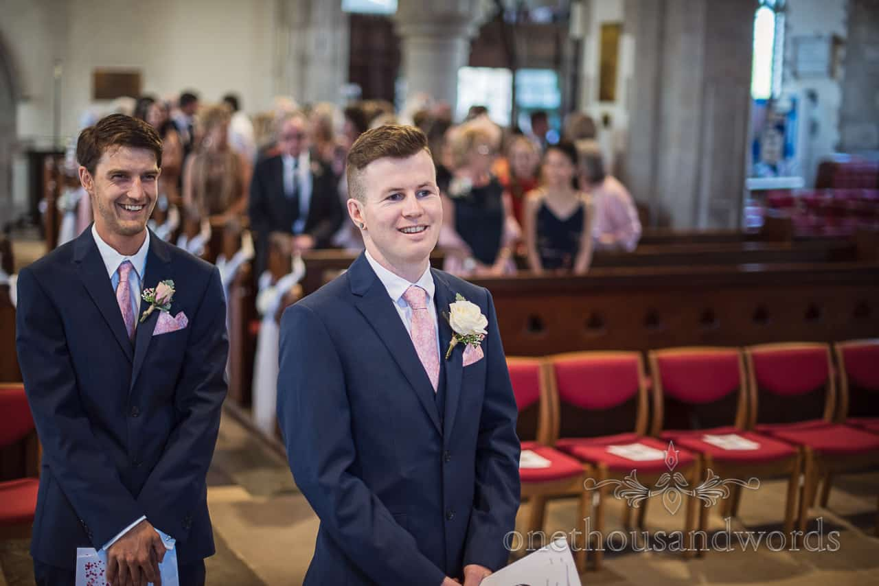 Smiling groom and Best Man in blue suits waiting for arrival of the bride before Swanage Church marriage ceremony with red chairs