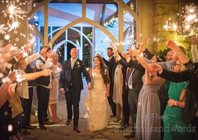 Bride and groom enjoy sparkler wedding exit photograph at Tithe Barn Dorset wedding venue surrounded by guests with sparklers