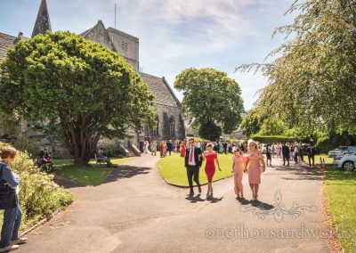 St Marys Church wedding venue in Swanage with wedding guests walking away in summer sun after wedding ceremony