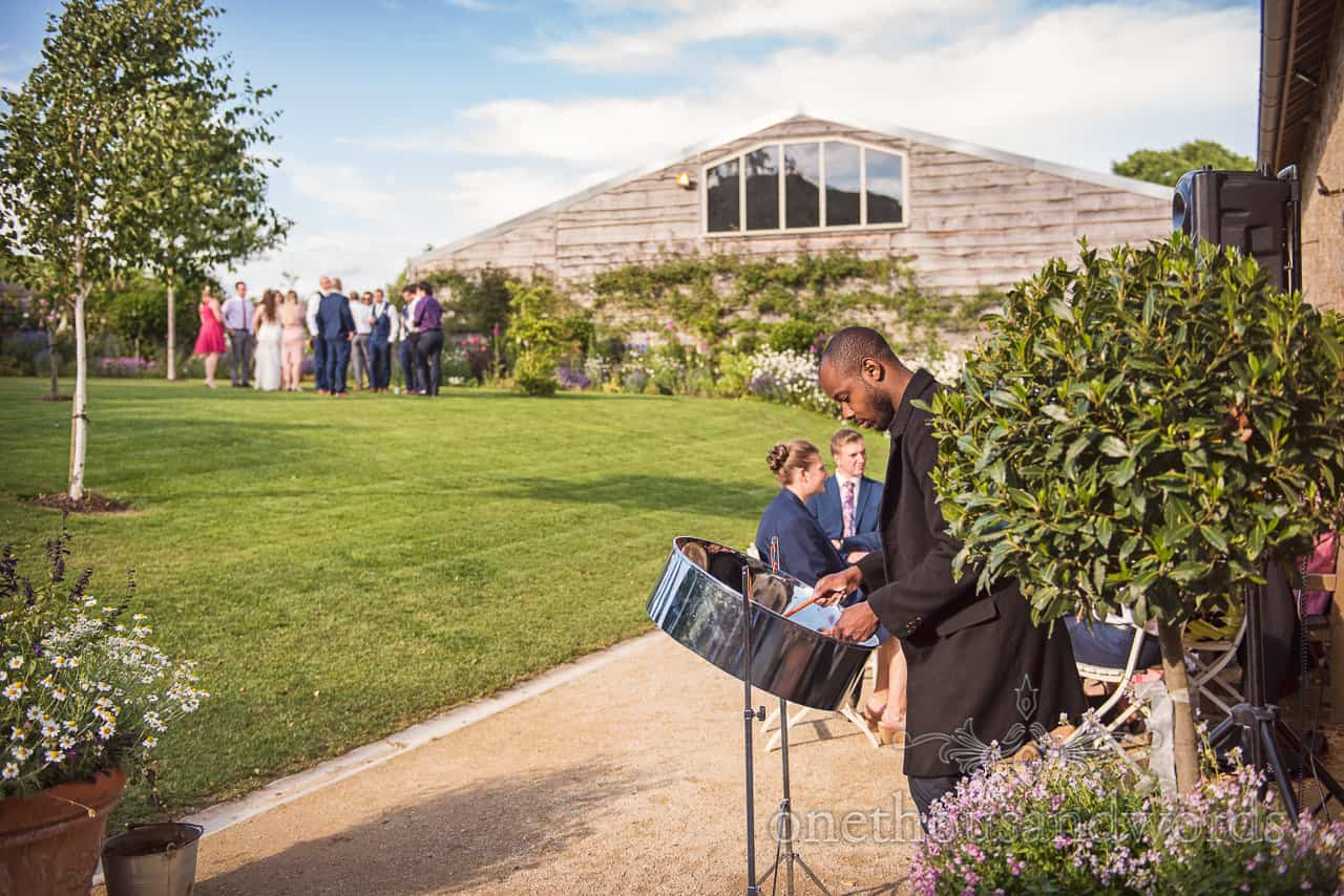 Steel drum musician playing as wedding drinks reception entertainment at Tithe Barn wedding venue garden in Dorset