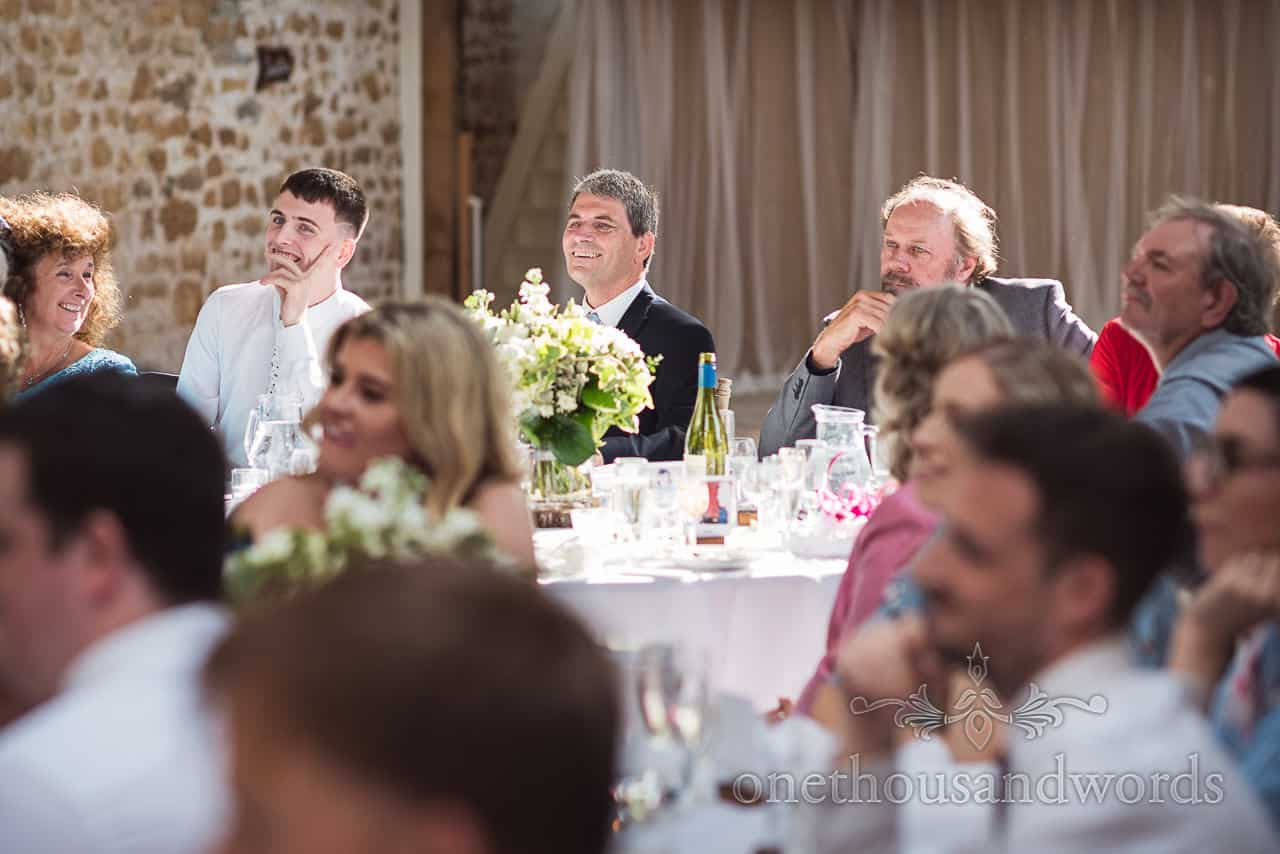 Wedding guests sat in sunlight laughing at wedding speeches in stone barn wedding venue photograph
