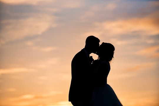 Candid silhouette of kissing bride and groom taken at sunset unaware they are having photo taken