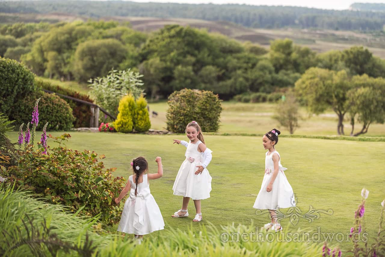 Three flower girls in white dresses playing games at Purbeck Golf Club Dorset countryside wedding venue photograph