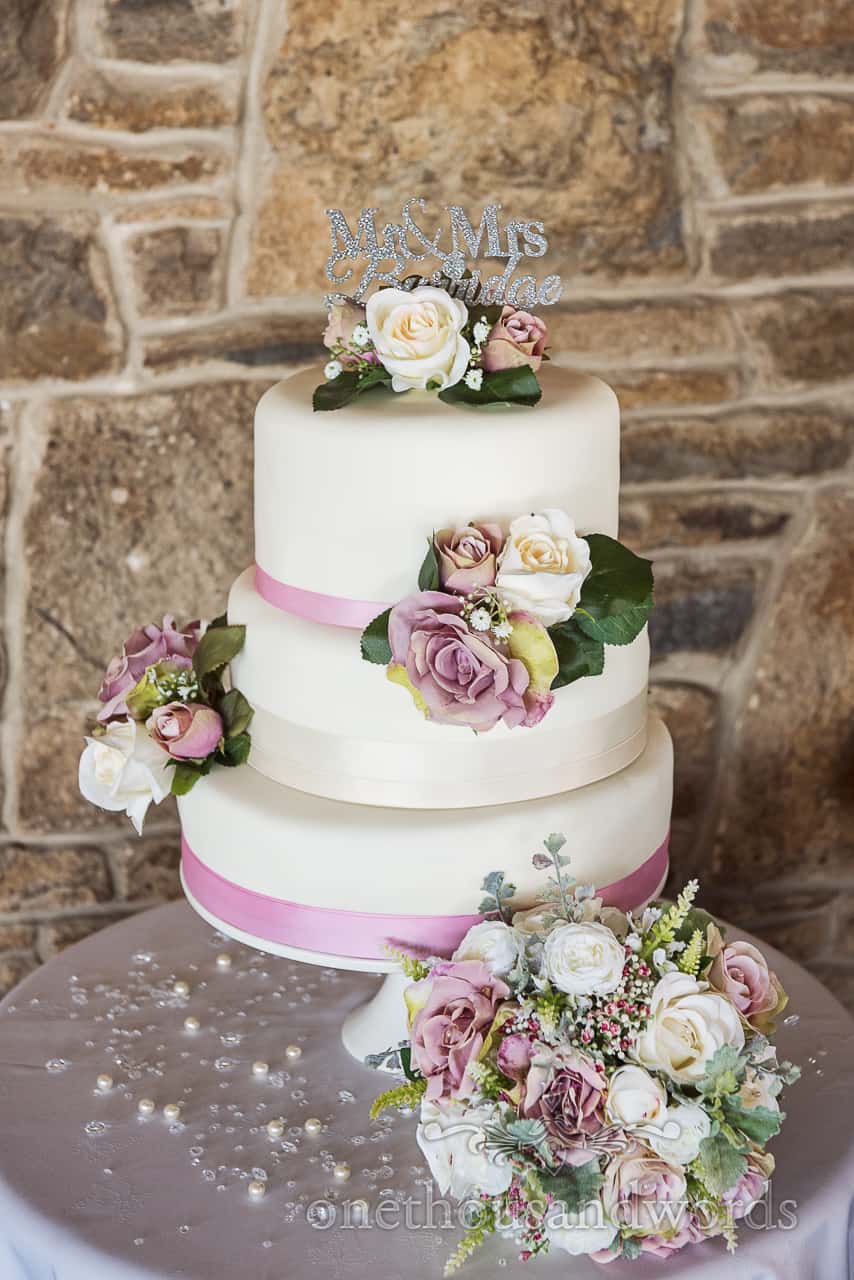 Three tier white wedding cake with pastel flowers and shiny silver name cake topper photo taken against stone wall