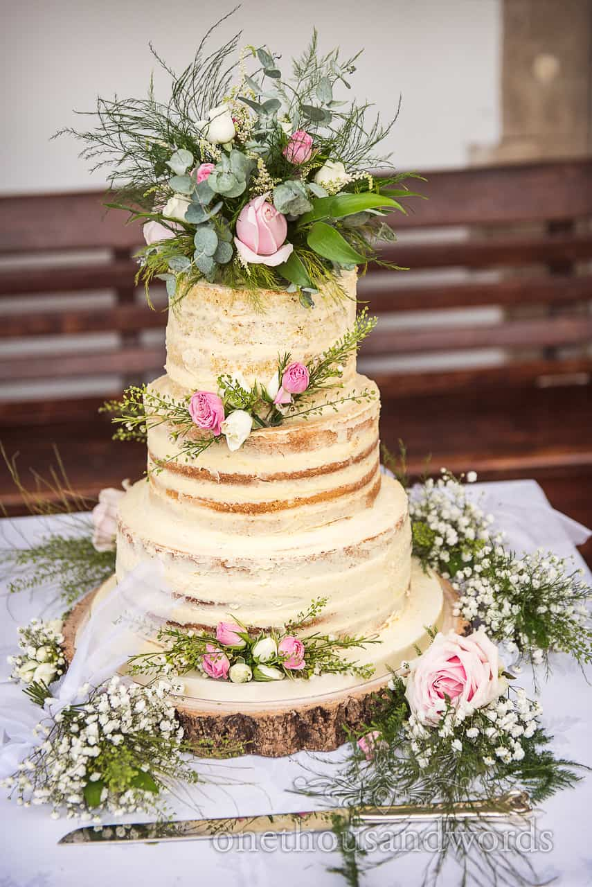 Three tiered butter iced Victoria sponge wedding cake with floral decoration on wooden log slice and silver knife