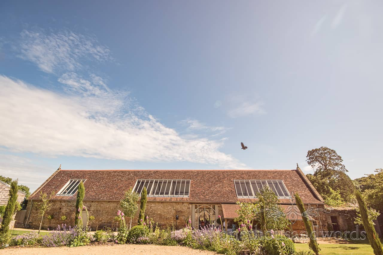 Tithe Barn Dorset wedding venue photograph on a summer's day with blue sky and green gardens