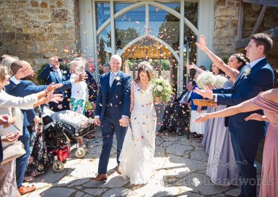 Bride and groom showered with petals by wedding guests at Tithe Barn Dorset wedding confetti photograph
