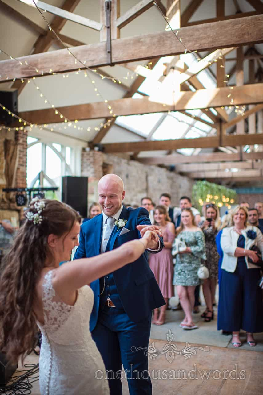 Groom in blue suit spins the bride during Tithe Barn Dorset wedding first dance watched by guests wedding photograph