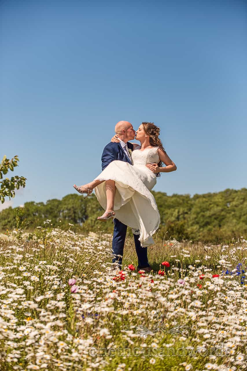 Tithe Barn Dorset wedding venue photograph of bride and groom kissing in countryside flower meadow