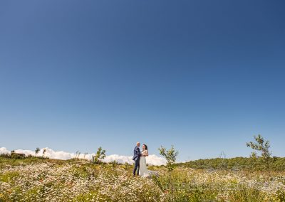 Tithe Barn Dorset wedding photograph of bride and groom in countryside flower meadow with blue summer sky