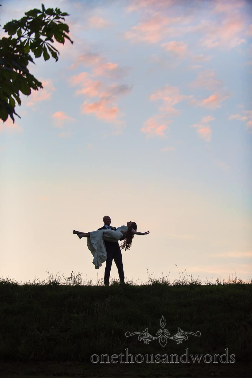 Tithe Barn Dorset wedding photograph at sunset of groom carrying bride with blue sky and red clouds by one thousand words