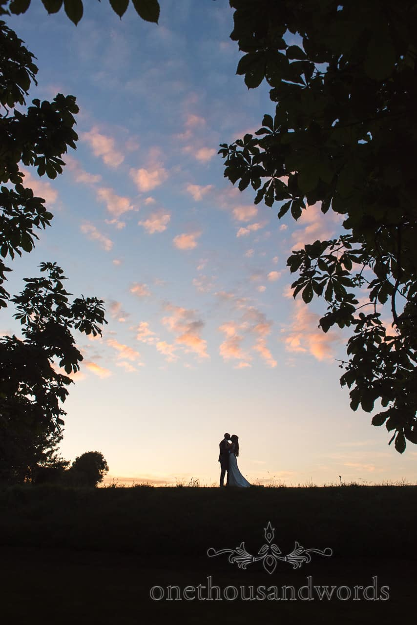 Tithe Barn Dorset wedding photograph at sunset of bride and groom in silhouette framed with trees by one thousand words photography