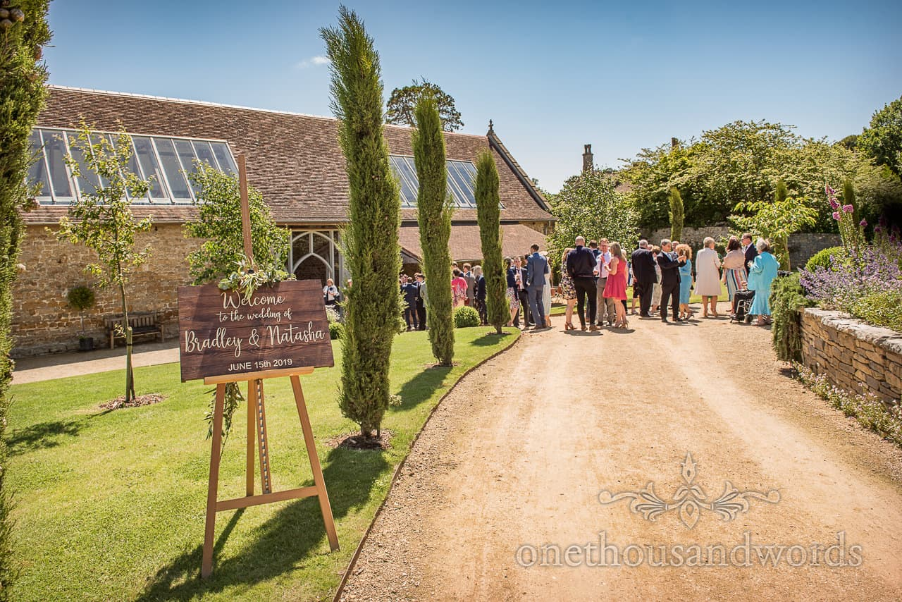 Tithe Barn Dorset wedding photograph of venue gardens with wooden welcome sign and guests enjoying drinks reception