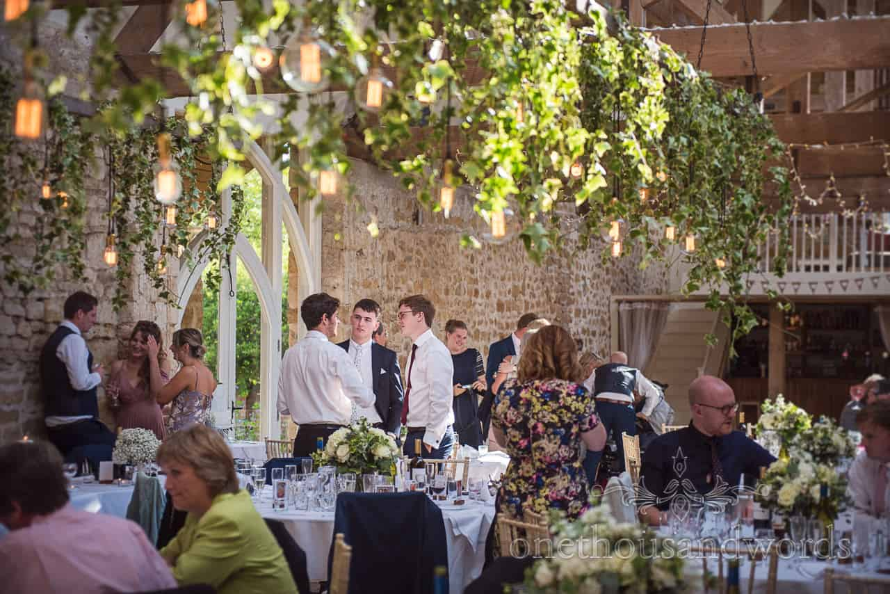 Tithe Barn Dorset wedding venue with hanging ivy and Edison bulbs during wedding breakfast interval photographs