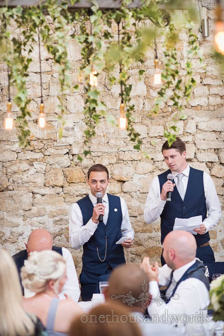 Two best men in blue wedding suits give wedding speeches under hanging ivy in stone Barn Dorset