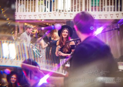 Lead singer of wedding band entertainment at Tithe Barn wedding in Dorset with coloured lighting and lens distortions
