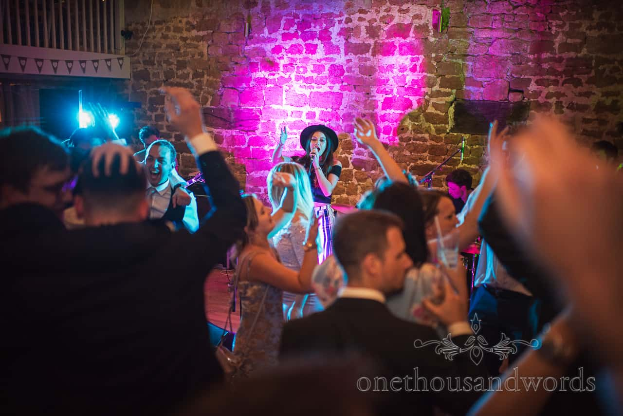 Wedding band singer with dancing wedding guests and coloured disco lighting at Tithe Barn Dorset wedding photograph