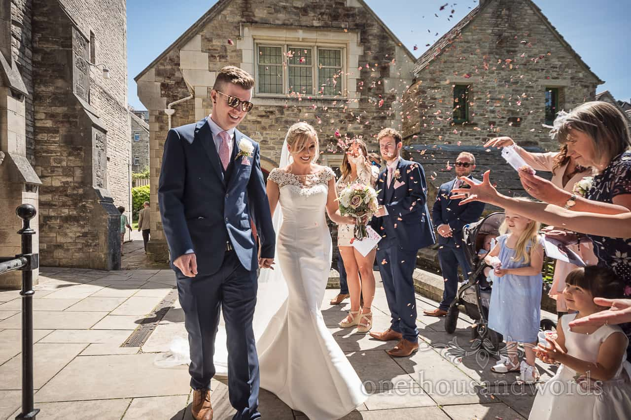 Wedding confetti photograph taken outside Dorset stone church after wedding ceremony as guests shower bride and groom