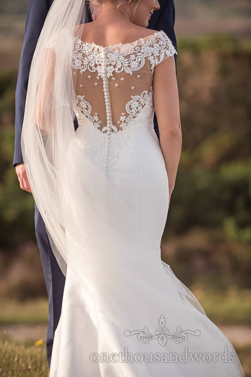 Wedding detail photograph of back of lace white wedding dress showing off brides curves