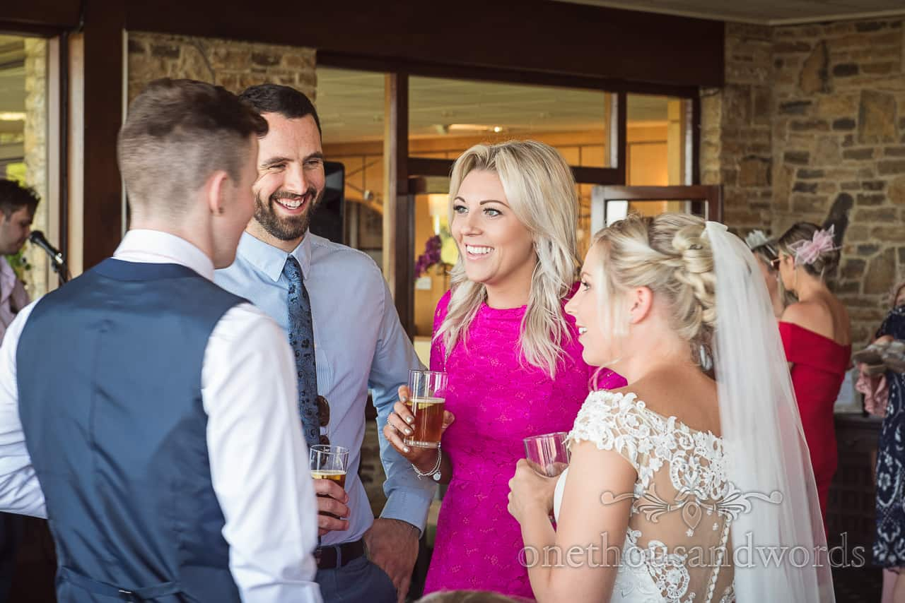Wedding drinks reception photograph at Purbeck Golf Club as bride and friends chat to guest wearing bright pink dress