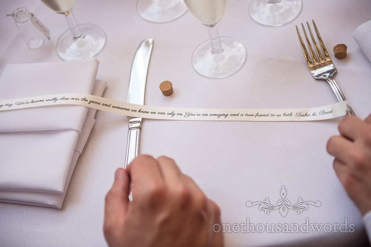 Wedding favour message in a bottle printed ribbon on white table cloth wedding detail idea detail photograph