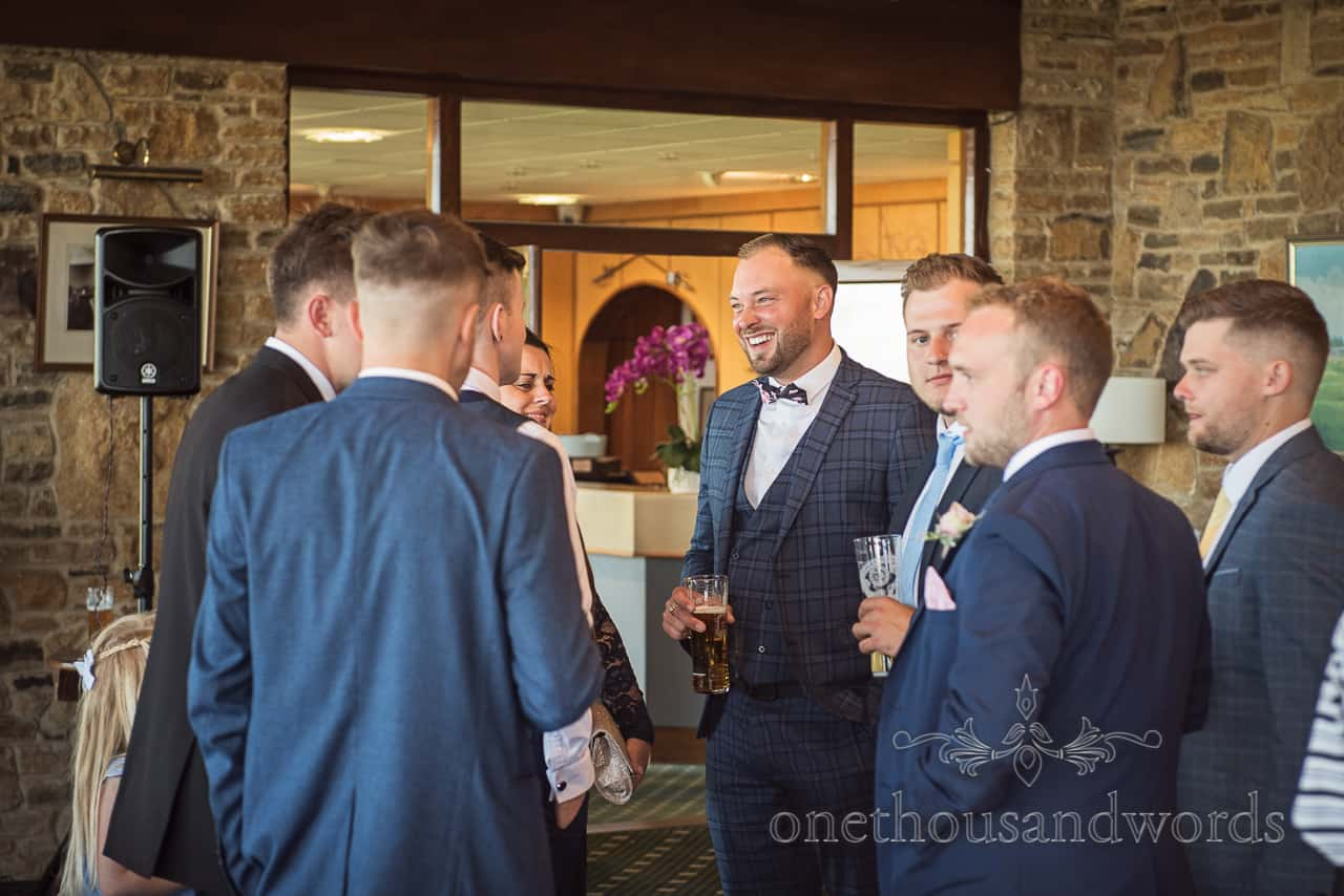 Wedding golf club drinks reception with laughing groomsmen wearing three piece check blue suit and bow tie holding beers