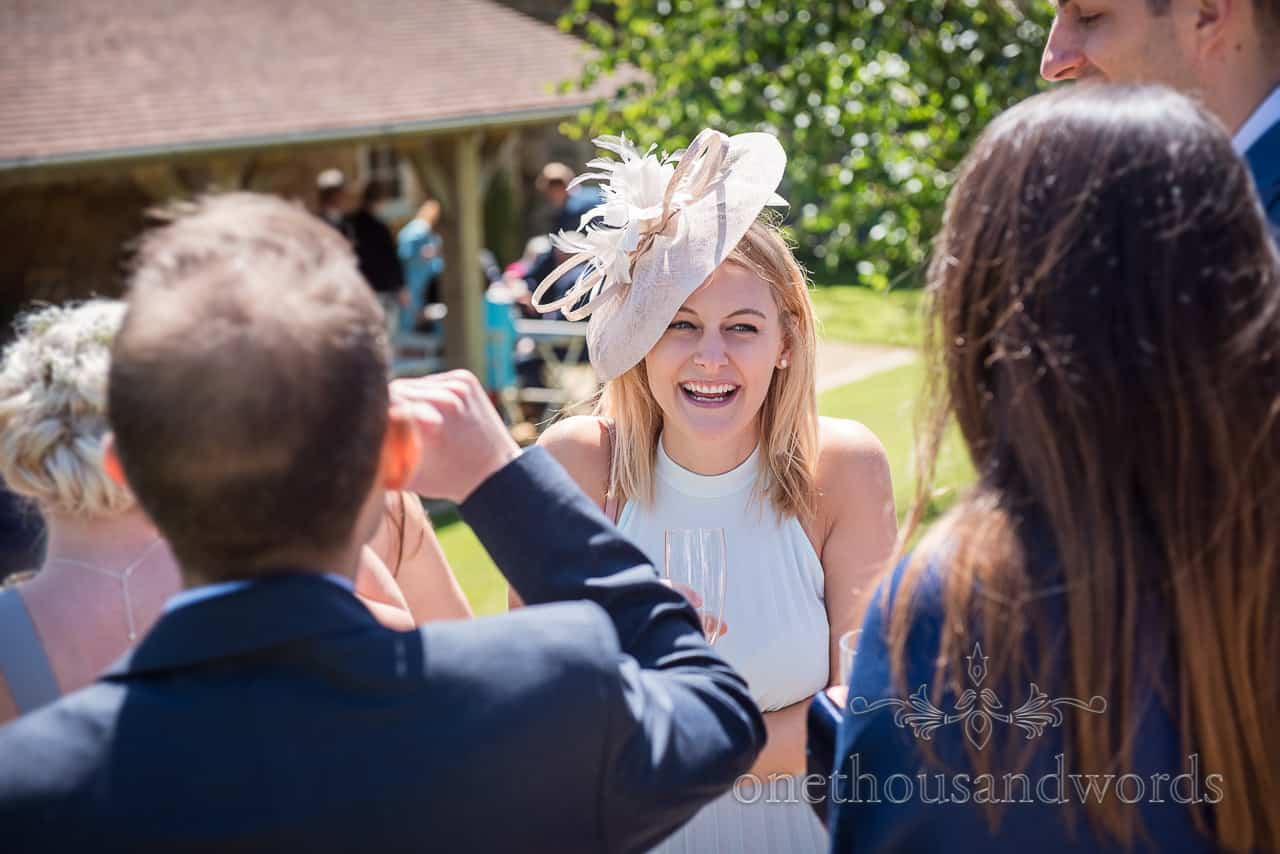 Wedding guest in pale blue dress wearing feathered hat laughing at garden drinks reception portrait photograph