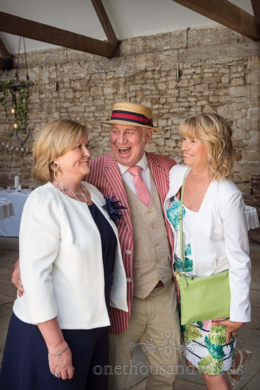 Wedding guest in straw boater laughing as he jokes with female wedding guests who have mixed reactions in stone barn