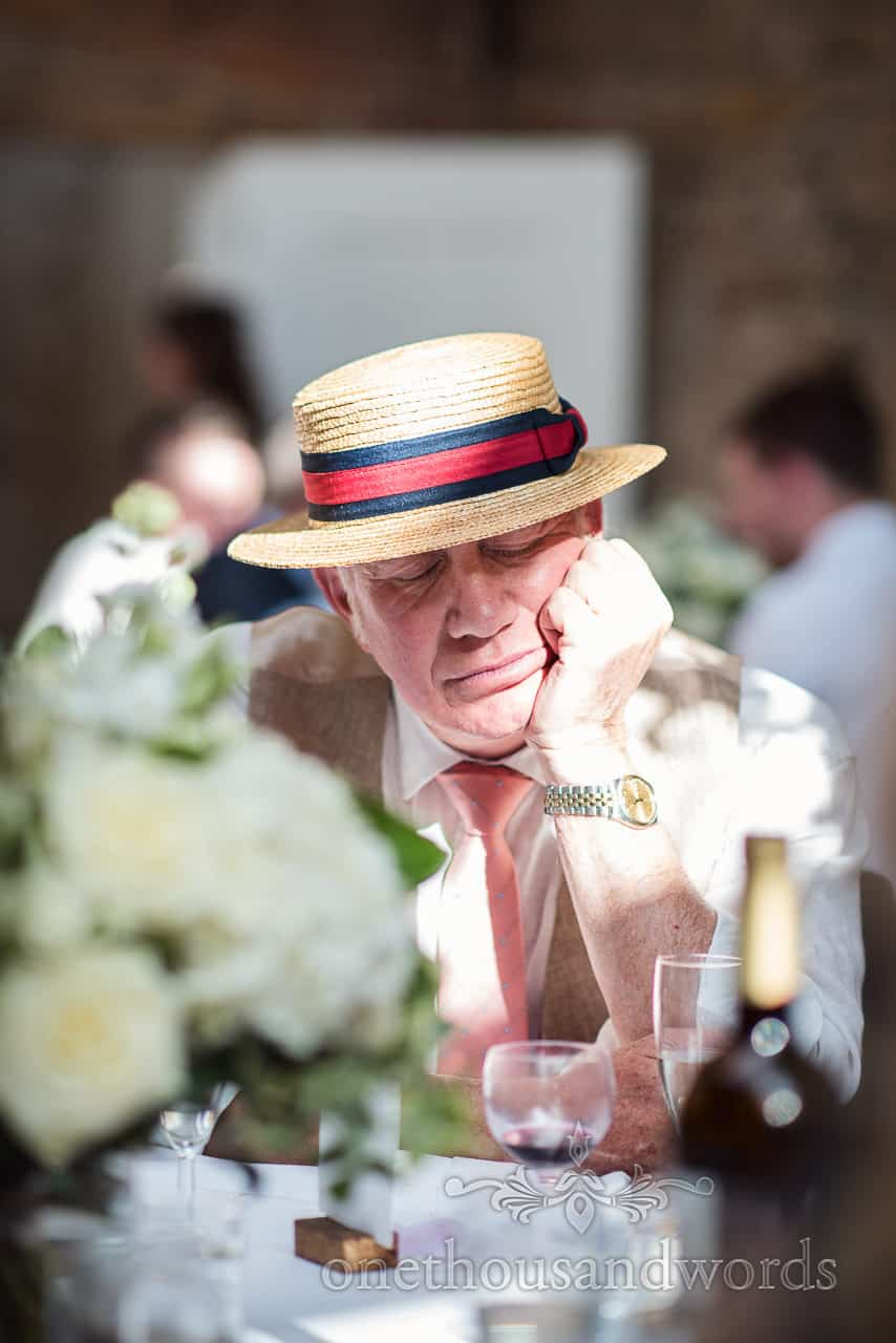 Wedding guest wearing retro straw boater falls asleep on his arm in the sunshine during wedding breakfast