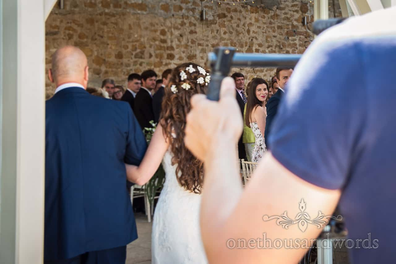 Smiling wedding guest watches bride and father's entrance to Dorset barn wedding ceremony through videographers arms