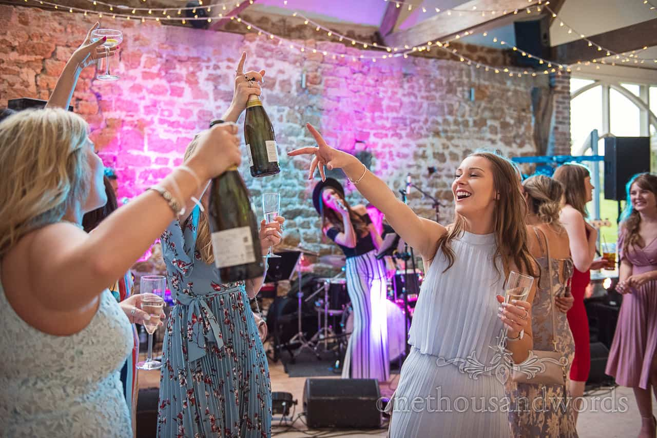 Female wedding guests dancing with Prosecco bottles and glasses at Dorset barn wedding venue evening