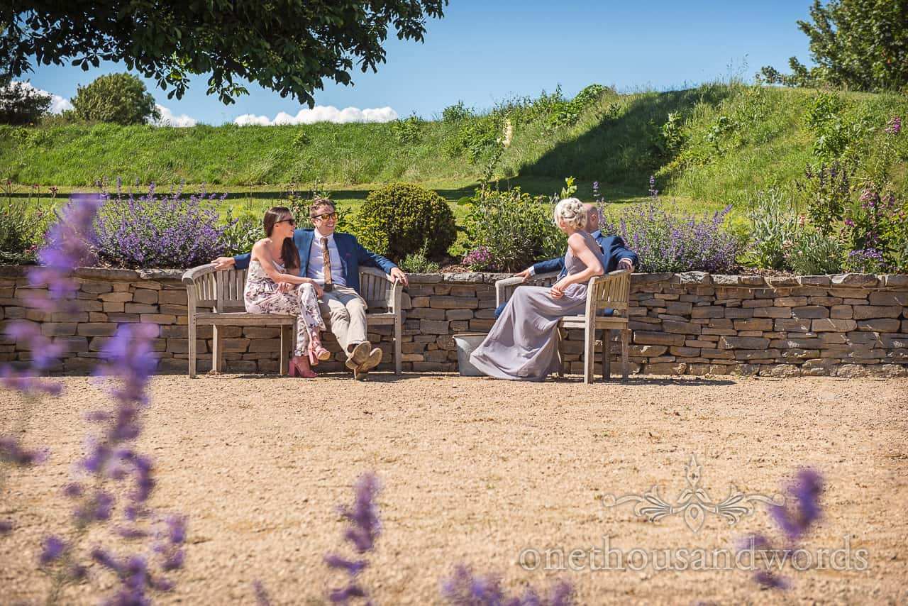 Wedding guests enjoy the summer sun sat laughing on wooden benches in the Tithe Barn Dorset gardens