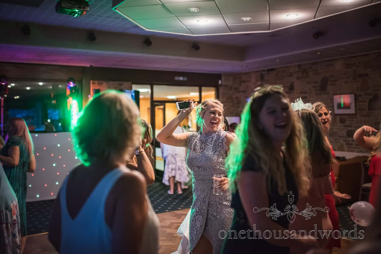 Wedding guests enthusiastic singing and dancing with phone in hand at wedding disco under coloured lights