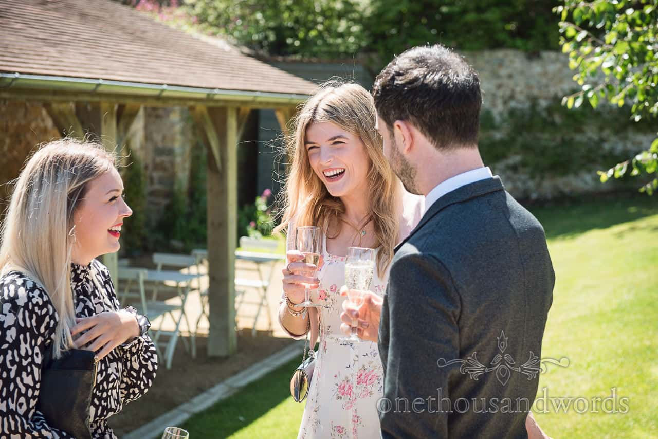 Laughing wedding guests in patterned dresses enjoy Dorset barn garden drinks reception in the summer sun