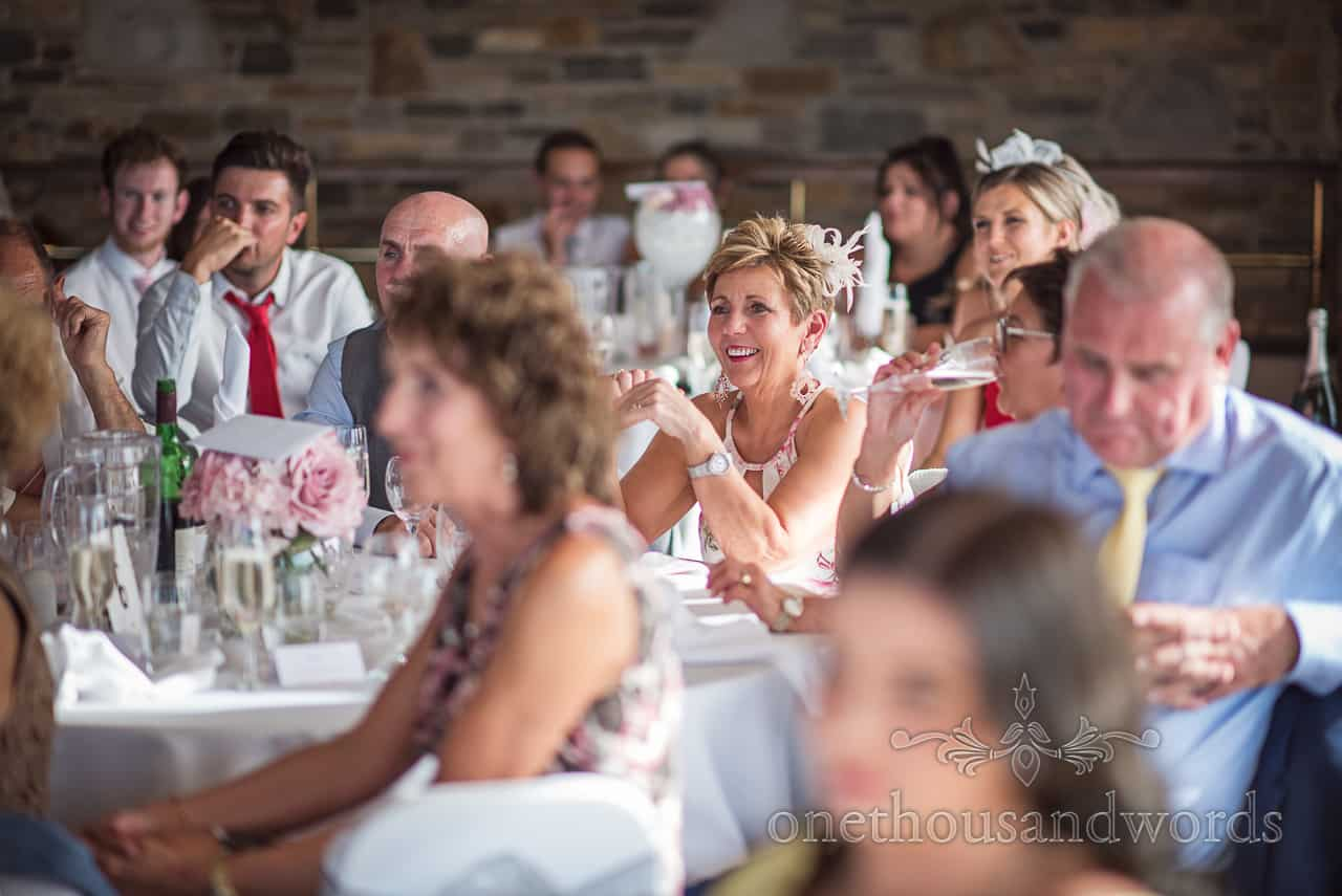 Wedding guest with white feather fascinator laughing during wedding speeches reaction photograph