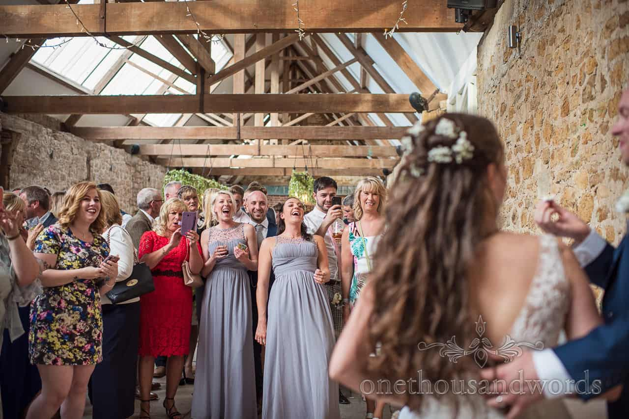 Wedding guests laughing at bride and groom cutting the cake in the Tithe Barn Dorset documentary wedding photograph
