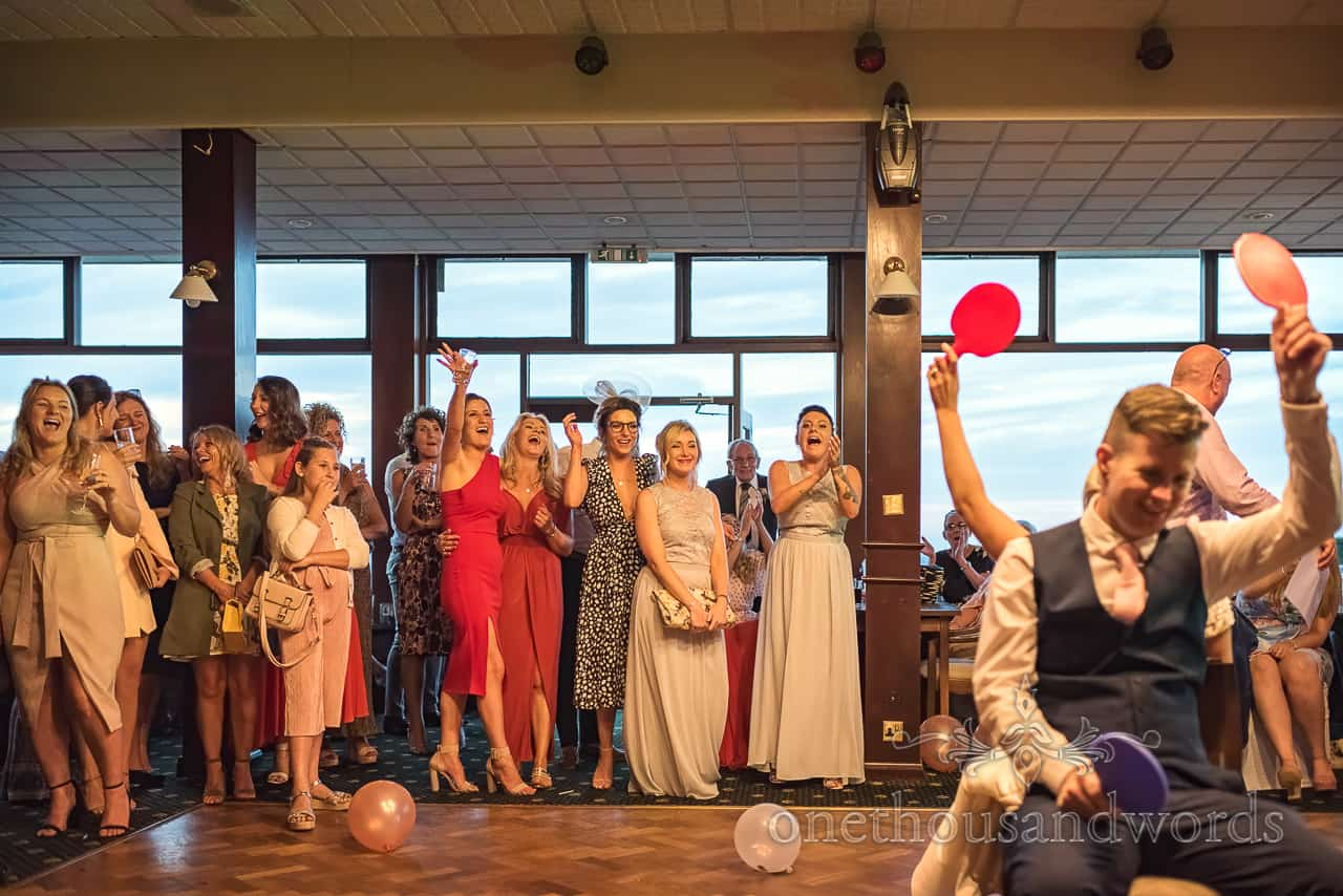 Wedding guests laughing reaction photograph of Mr and Mrs Game on dance floor holding up coloured paddles to answer questions