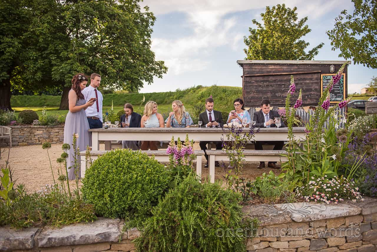 Wedding guests sit in a line at a wooden table on phones and chatting in the Tithe Barn wedding venue gardens