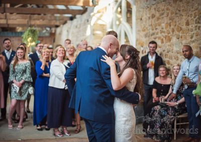 Wedding guests stand around dance floor and watch bride and groom laughing during first dance in stone barn