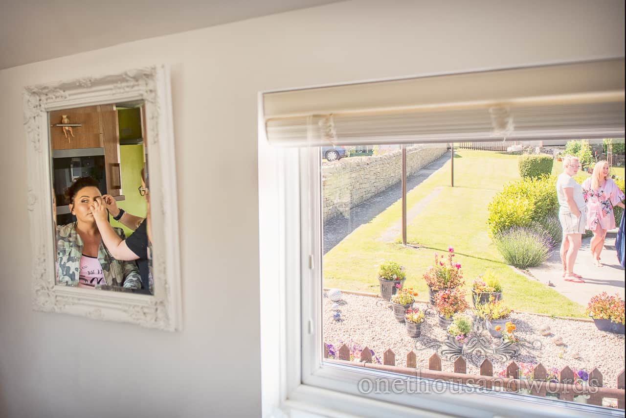 Bridesmaids wedding make up styled in ornate white mirror on wedding morning with summer garden window view
