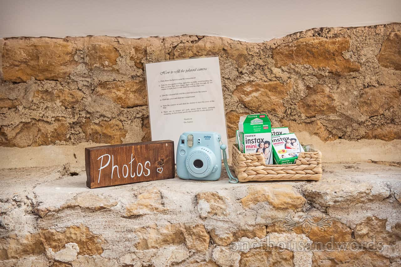 Wedding photo booth alternative Polaroid camera with instructions, photo sign and spare film in basket on stone wall