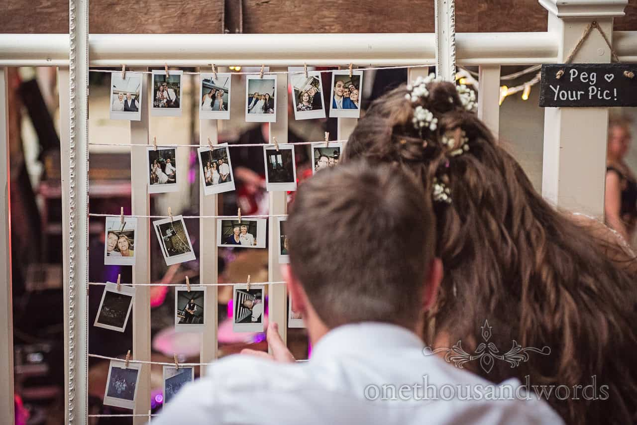Wedding Polaroid pictures photo booth alternative hanging on pegs and string frame inspected by bride on wedding day