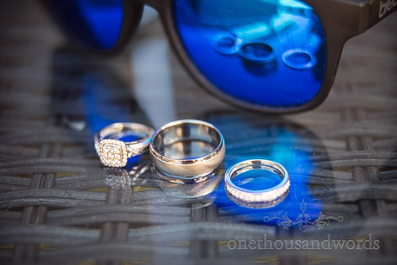 Wedding rings reflection in glass table and blue tinted sunglasses wedding detail photograph by one thousand words