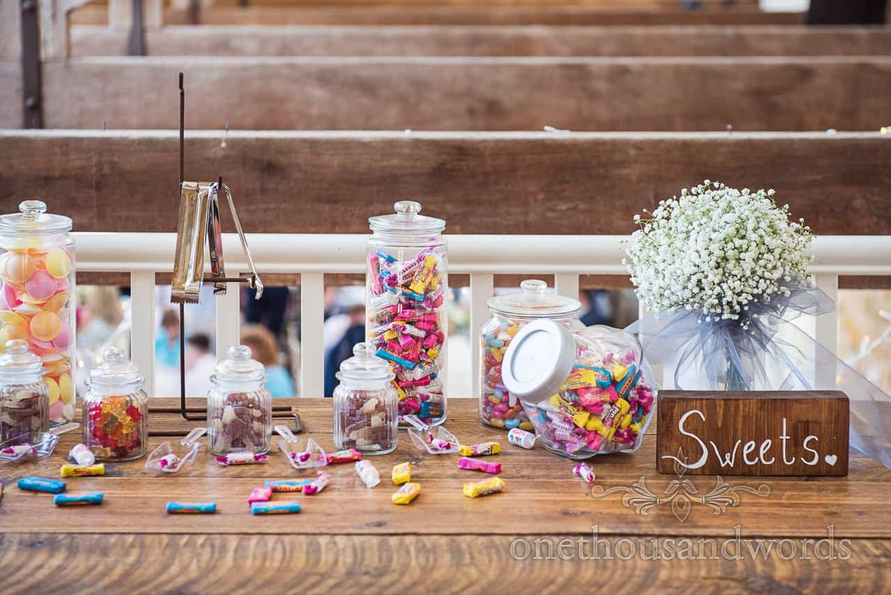 Wedding sweets in plastic jars DIY sweet table idea wedding detail photograph with wooden sweets sign and gypsophila bouquet