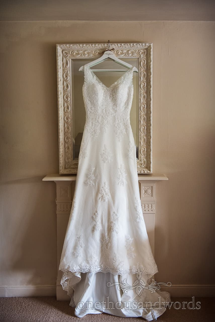 White detailed wedding dress hanging on ornate framed mirror over fireplace during wedding morning preparations